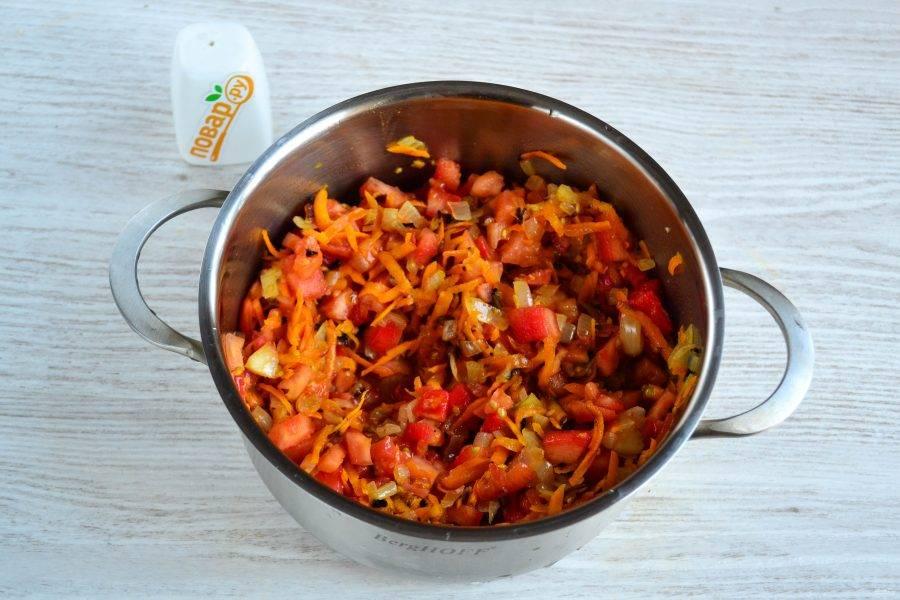 В кастрюлю с толстым дном переложите обжаренные морковь и лук, туда же отправьте нарезанные помидоры.