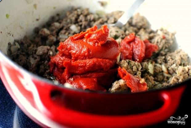5. Выложите небольшими порциями томатную пасту, постоянно помешивая. На первый взгляд может показаться, что это слишком много, но поверьте: соус должен быть по-настоящему томатным.