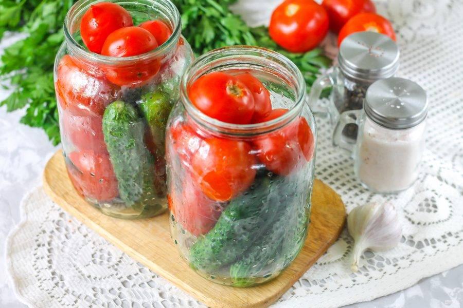 Промойте огурцы и помидоры. По желанию с огурцов можно срезать окончания с обеих сторон. Поместите в промытую банку сначала огурцы, полукругом, затем выложите помидоры, стараясь их сильно не давить.