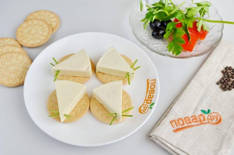 2. Ка крекер положите по сырному треугольничку. Из веточек петрушки сделайте усики: просто воткните в сыр небольшой кусочек веточки.