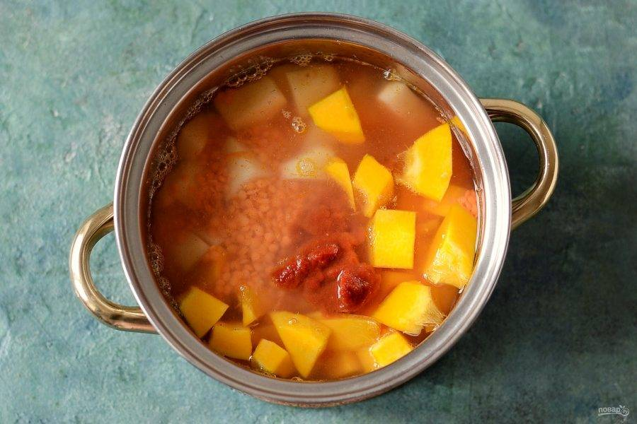 Следом добавьте  промытую чечевицу и томатную пасту. Влейте воду. Доведите до кипения, затем убавьте огонь. Варите суп 20-25 минут на средне-низком огне, пока картофель и тыквы не станут мягкими, а чечевица не разварится.