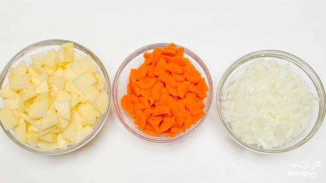 2. Очистите и нарежьте мелко овощи. В кипящую воду добавьте по вкусу соль, всыпьте рис, отправьте следом лук и морковь.