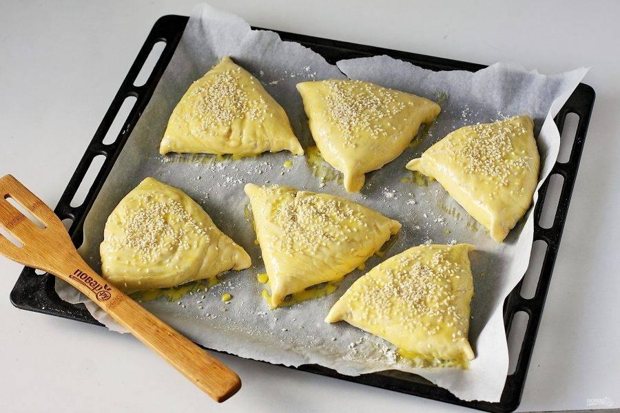Переложите самсу на противень, дайте ей немного подойти, затем смажьте желтком и посыпьте кунжутом. Выпекайте в духовке при температуре 180-200 градусов около 40 минут.