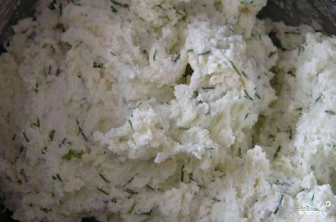 В творожную массу натрите сыр на крупной тёрке. Также добавьте зелень, муку и разрыхлитель. Всё хорошо перемешайте.
