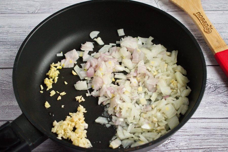 2.     Мелко нарежьте лук, чеснок, имбирь. Обжарьте  на разогретом растительном масле в течение 2 минут, периодически помешивая.
