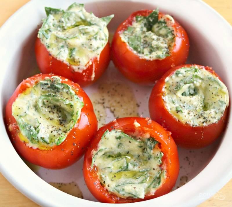Затем наполните помидоры начинкой. Поставьте их в форму для запекания. Сверху сбрызните блюдо маслом. Посыпьте солью и перцем.