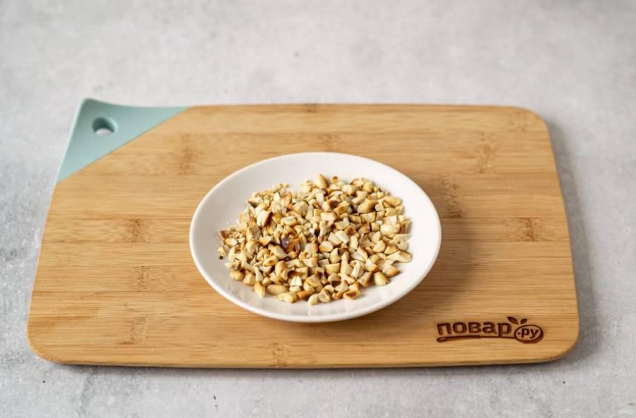 В сухой сковороде обжарьте арахис до золотистого цвета. Очистите его от шелухи и крупно порубите ножом.
