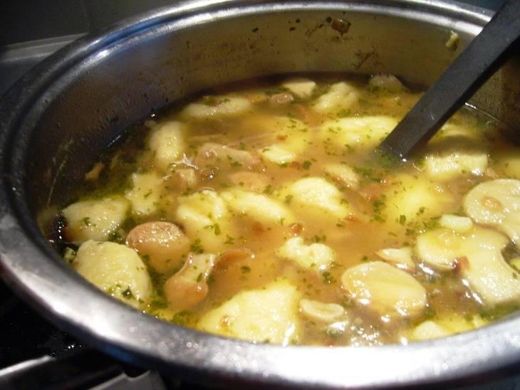 Бросьте в суп грибы и, с помощью чайной ложки, выложите небольшими порциями тесто для галушек. Дайте покипеть 5 минут. Затем добавьте зелень, перемешайте и снимите с огня. Можно сразу подавать на стол.