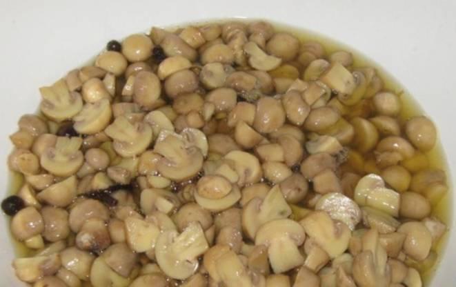 Приготовим маринад. Кипятим в кастрюле воду и уксус. Добавляем соль, перец и специи. В кипящий маринад опускаем грибы, снова доводим до кипения, удаляя пену. Варим еще 25 минут. Кастрюлю снимаем с плиты и сразу же ставим в таз с холодной водой, чтобы быстро охладить грибочки.