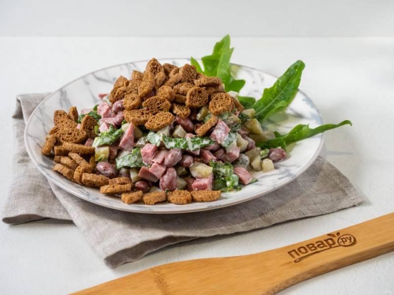 Выложите салат на общее блюдо или порционно, сверху посыпьте сухариками.