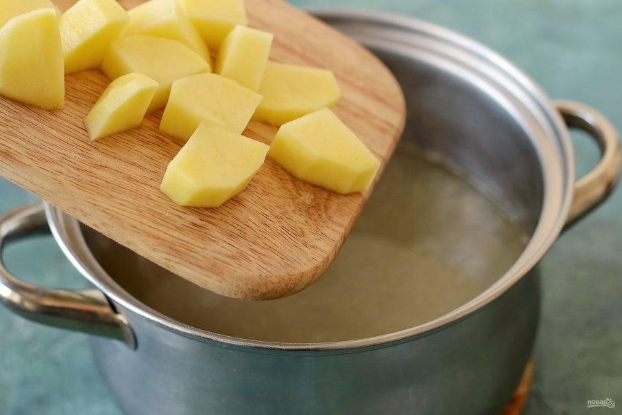 Залейте чечевицу водой и поставьте вариться на среднем огне на 15 минут. Картофель помойте, очистите и нарежьте на крупные кубики. Добавьте в кастрюлю и варите еще 10 минут.