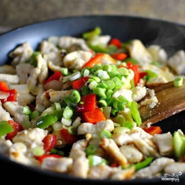 Когда курица покроется небольшой корочкой (точнее, не сама курица, а обволакивающий ее крахмальный кляр), добавляем обжаренные овощи, а также свежий нарубленный зеленый лук.
