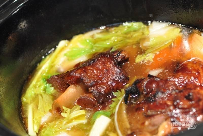 1.Сперва сделайте бульон: в кастрюлю выложите копченую рульку на кости, залейте её водой, добавьте 1 луковицу, 2 моркови и 1 стебель сельдерея, нарезанные крупно. Варите 2-3 часа на слабом огне. Достаньте рульку, процедите бульон и избавьтесь от овощей, очистите мясо.
