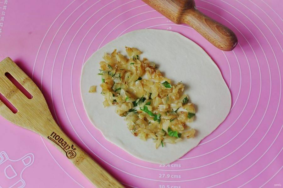 От теста отщипните кусочек, скатайте его в шарик размером примерно чуть больше грецкого ореха, а затем раскатайте скалкой в форме круга. Ближе к одному краю выложите начинку. Не забывайте, что чебуреки — это не пирожки, много не надо, достаточно буквально 2-3 ч.л.