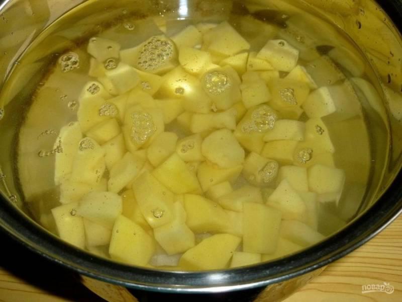 2. Сразу нарезаем картофель кубиками и заливаем холодной водой. Ставим на плиту и доводим до кипения. Солим и приправляем по вкусу.