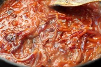 Влейте томатную пасту к луку и пожарьте еще 2 минуты.