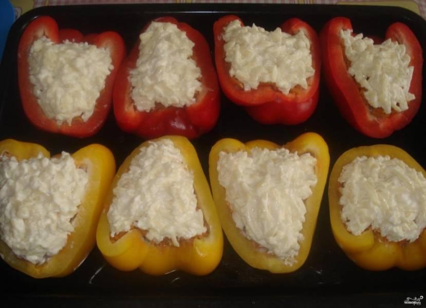4. Перцы моем, разрезаем на 2 половинки, удаляем у них ножку и семена. В каждую вкладываем фарш, сверху кладем слой морковки, а после этого — сыр с майонезом. Противень или форму для выпекания смазываем подсолнечным маслом, выкладываем в неё фаршированные перцы, выпекаем их в разогретом до 180 градусов духовом шкафу около 50 минут. Готовые перцы подаем со свежей зеленью.