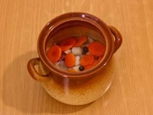 Сверху положите немного лука и моркови. Добавьте в каждый горшочек по несколько горошин перца. Налейте воду, чтобы закрыть мясо, лук и морковь. Закрываем горшочки крышечками и отправляем в духовку на 30 минут, температура 180 градусов.