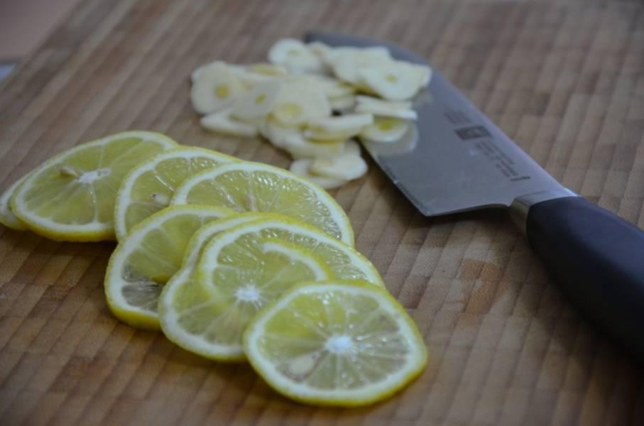 Порежьте лимон кольцами, чеснок дольками.