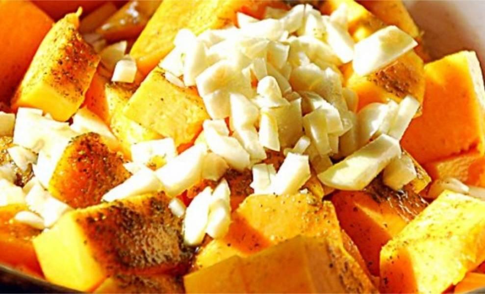 2. Тыкву нарежьте кубиками, добавьте столовую ложку тыквенных семечек. Посолите, добавьте хмели-сунели, столовую ложку оливкового масла и зубчик мелко-нарезанного чеснока. Оставьте также на 20 минут.