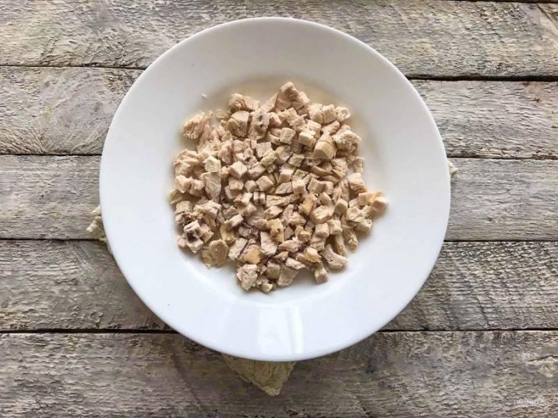 Отварное куриное филе, мелко нарежьте и выложите на дно тарелки.