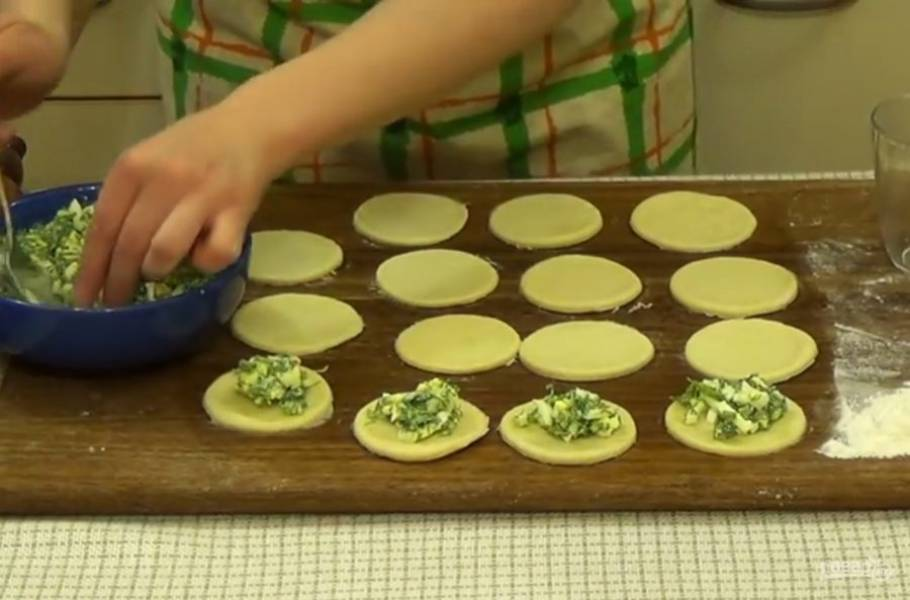 4. Тесто слегка вымесите и раскатайте в пласт толщиной 3-4 мм. Вырежьте круги из теста и выложите начинку. Соедините края пирожка так, чтобы шов был снизу.