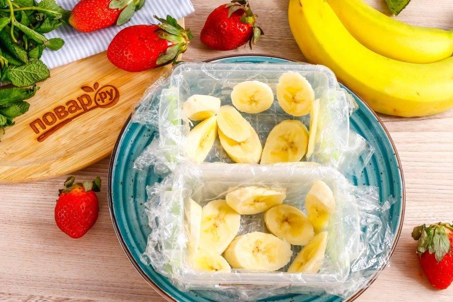 Емкость для террина застелите пищевой пленкой. Если готовите порционные десерты, то каждую емкость выстелите пленкой. Банан очистите от кожуры и нарежьте ломтиками, выложите на дно емкости и на бока.