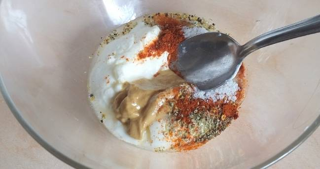 1. Подготовьте маринад для грудки индейки. Для этого возьмите йогурт и выложите в миску. Добавьте в него дижонскую горчицу, посолите. Положите ваши любимые специи (лучше смесь для мяса птицы). Тщательно перемешайте.
