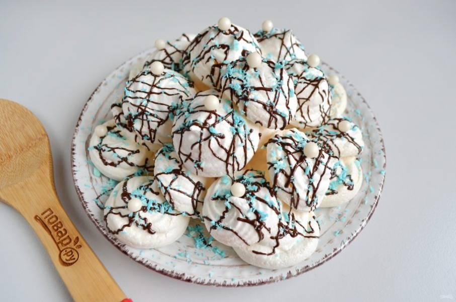 7. Готовые безешки сложите горкой, полейте теплым шоколадом, посыпьте синей кокосовой стружкой, положите сахарные бусинки для украшения.