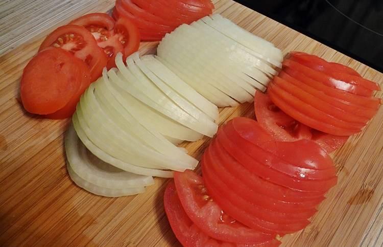 Тем временем режем оставшийся лук и помидоры тонко кольцами.