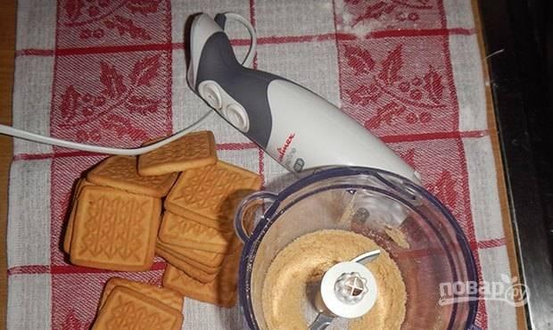 Возьмите песочное печенье и поломайте его на куски. Положите кусочки печенья в чашу блендера и превратите печенье в мелкую рассыпчатую крошку.
