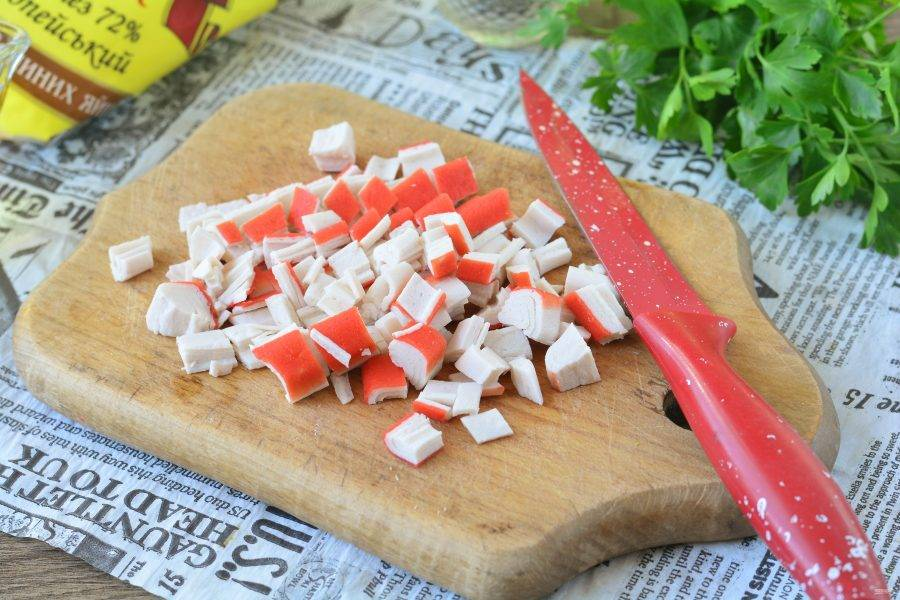 Нарежьте средними кусочками крабовые палочки.