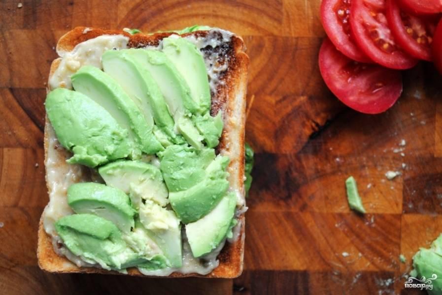 Закрыть сэндвич куском хлеба, нанести другой соус и выложить кусочки авокадо сверху.