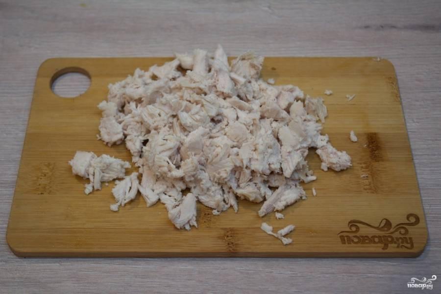 Из бульона достаньте куриное мясо. Остудите его и нарежьте мелко.