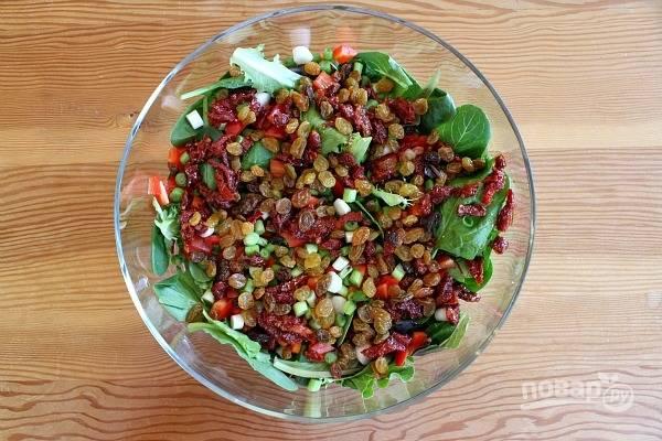 Следом добавьте кусочки томатов и промытый изюм.