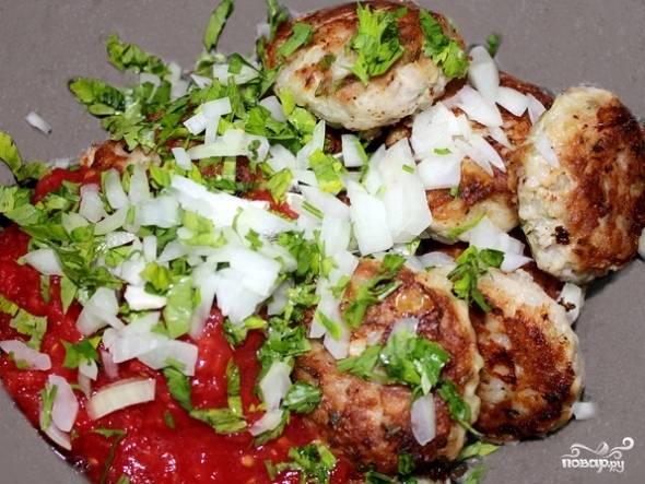 Перекладываем обжаренные тефтели в казанок или глубокую кастрюлю и добавляем к ним измельченные помидоры, оставшийся лук и зелень.