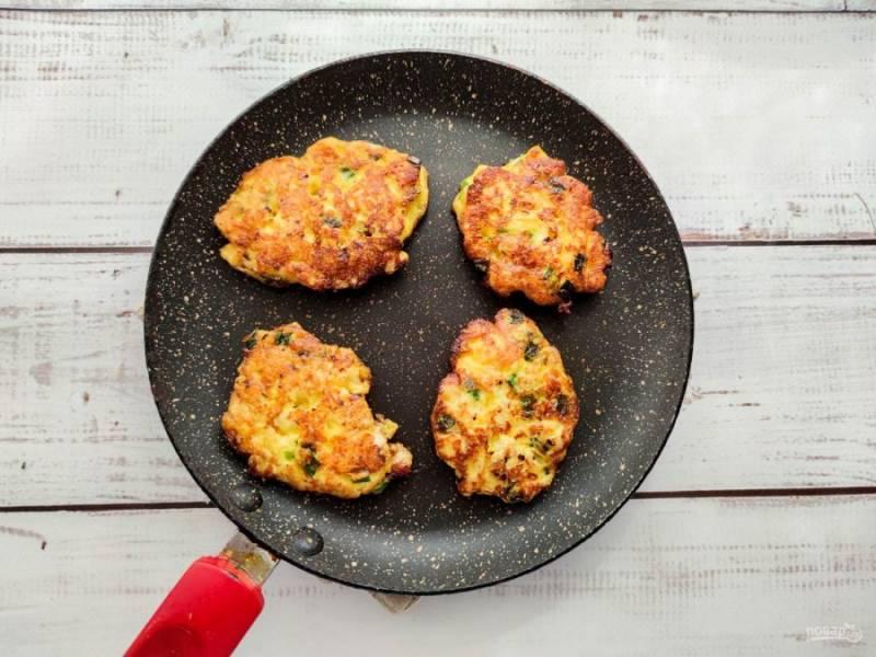 Обжарьте куриные оладьи в хорошо разогретой сковороде по 2-3 минуты с каждой стороны.