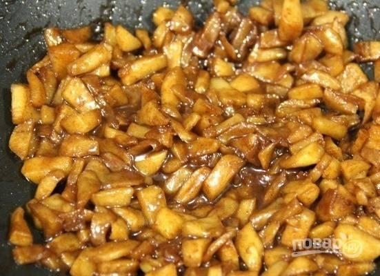 4. Выложите яблоки на сковороду с растопленным сливочным маслом. Добавьте тростниковый сахар и ложку корицы. Томите на огне, помешивая, до мягкости. Снимите яблоки и остудите.