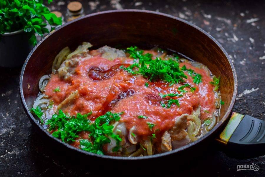 Добавьте в сковороду помидоры. Также можете добавить еще немного острого соуса или аджики - это дело вкуса. Нарежьте зелень, бросьте горсть зелени в сковороду. Тушите курицу 25 минут. Спустя время разложите блюдо по тарелкам.