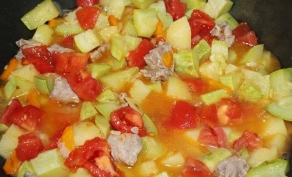 Добавляем порезанные помидоры, вливаем бульон и тушим на медленном огне до готовности овощей.