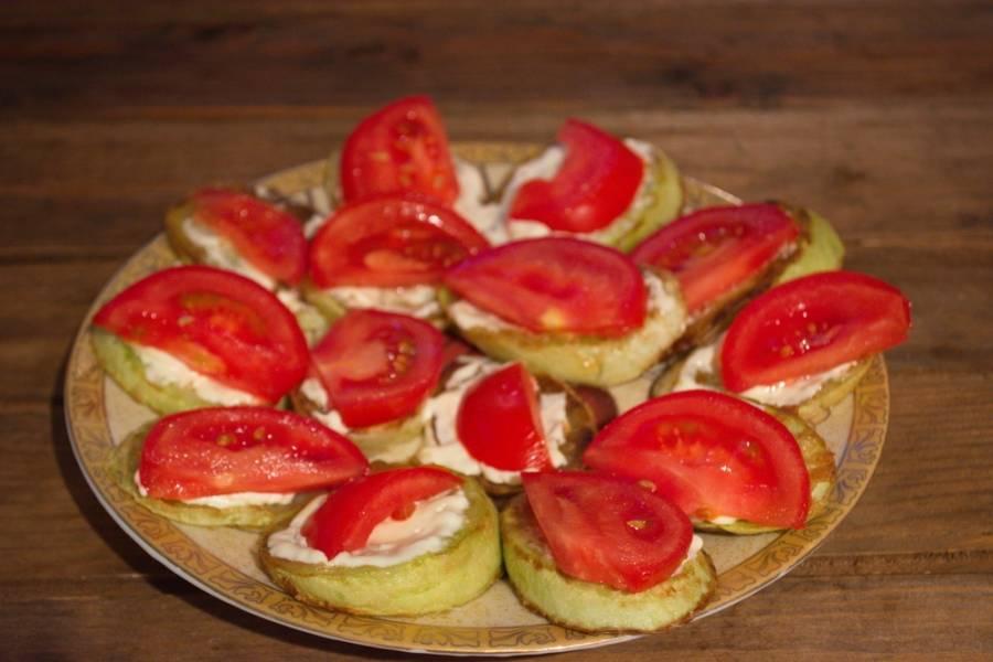 Смажьте кабачки смесью майонеза и чеснока. Вместо майонеза можно использовать сметану, но в нее следует добавить соль, специи по вкусу. На каждый кусочек кабачка выложите по кусочку помидора.