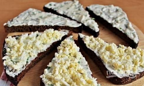 На хлеб с соусом выложите измельченное отварное яйцо. Равномерно его распределите по всей поверхности тостов.