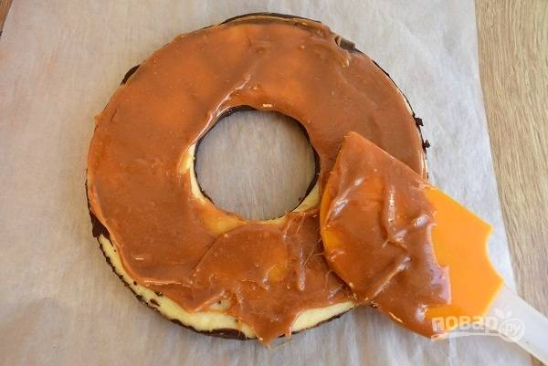 Переверните основу шоколадной стороной вниз. Часть карамели намажьте на песочное кольцо. Работайте быстро, чтобы карамель не успела застыть.