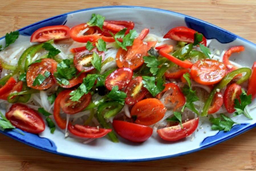 Выложите на рыбу лук и перец, затем разложите половинки помидорок. Посолите, поперчите, присыпьте орегано и петрушкой. Запекайте треску с овощами в разогретой до 200 градусов духовке 20 минут.