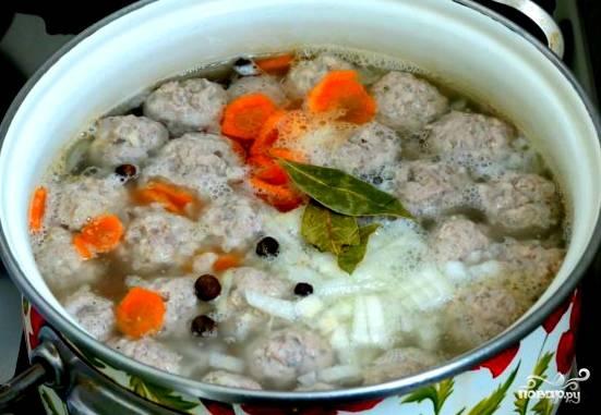 Пока закипает вода в кастрюле, режем остальные овощи. Картошку — кубиками. Морковь — кружочками. Когда вода закипит, опускаем в нее фрикадельки. Они должны вскипеть, после чего снимаем накипь. Кладем картошку, морковку, перчик горошком, лавровый лист, досаливаем.