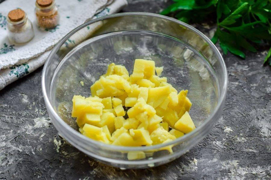 Картофель отварите и остудите, нарежьте небольшими кубиками и выложите в салатник.