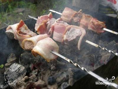 Теперь подготовьте мангал, наденьте на каждую шпажку (шампур) по 4 кусочка телятины, как бы завернув каждый в бекон.