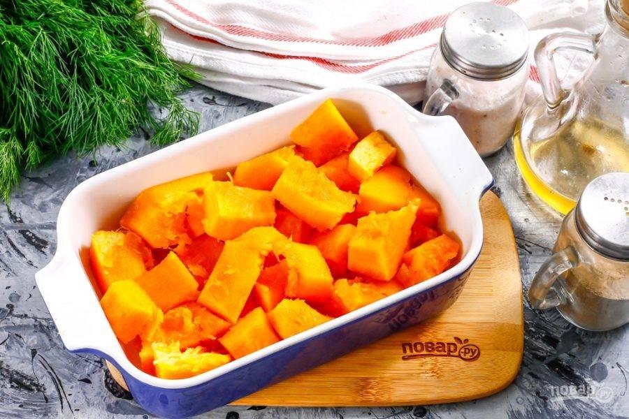 3. Тыкву и яблоко промойте в воде, срежьте с части тыквы кожуру, очистите от семян и промойте еще раз, нарежьте средними кубиками. Смажьте форму для запекания оставшимся растительным маслом и выложите в нее тыквенную нарезку, посолите.