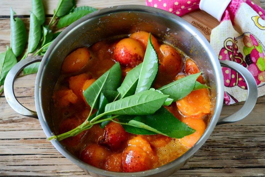 Поставьте кастрюлю с абрикосами на медленный огонь и доведите до кипения. Проварите 5 минут и снимите с огня. Оставьте варенье на 2-3 часа и снова поставьте на огонь. На этом этапе положите в кастрюлю листья вишни, ополоснув их холодной водой. Я кладу листья прям на веточке, тогда их легче вынимать потом. Двух веточек будет достаточно. Варите варенье на медленном огне 15 минут, аккуратно помешивая, стараясь меньше повреждать абрикосы.