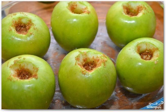 Берем форму для выпекания, слегка смазываем сливочным маслом. Выкладываем в нее яблоки. Каждое яблоко начиняем нашей ореховой смесью.